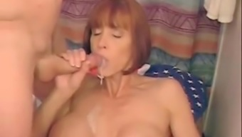 Red-Haired Milf With Big Silicone Titties Stinks And Blows An Enormous Dong